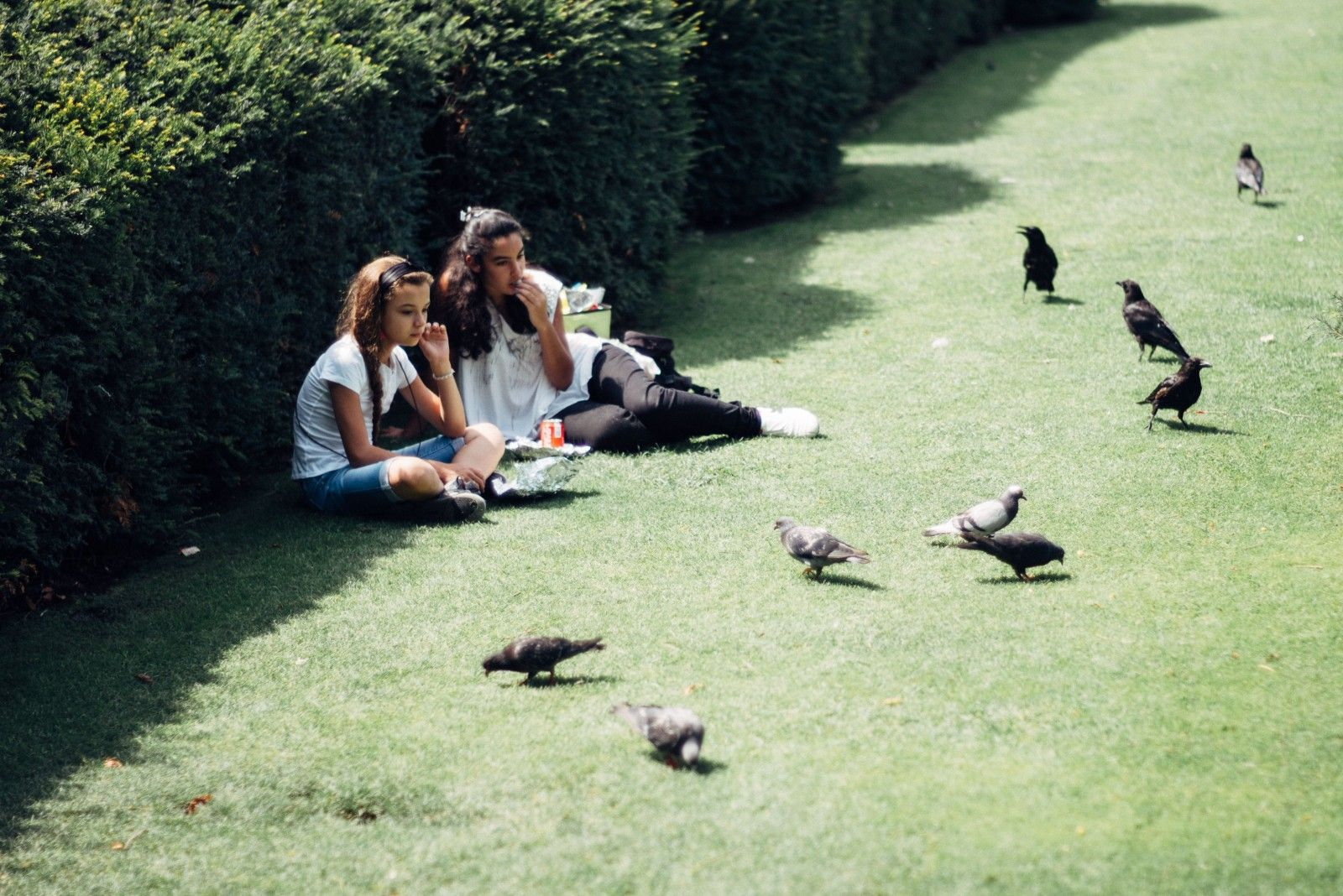 Two young girls having lunch in the park.